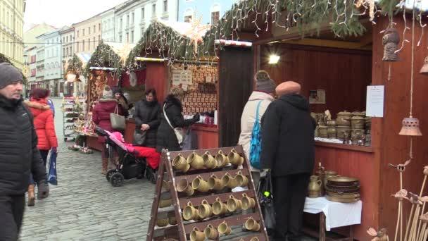 Olomouc, Česká republika, 17 prosince 2017: Lidé na adventním vánočním trhu stání na náměstí, prodej keramických zvony, poháry a nádobí, křesťanské svátky lidí, kteří jdou, Evropa, Evropského unie
