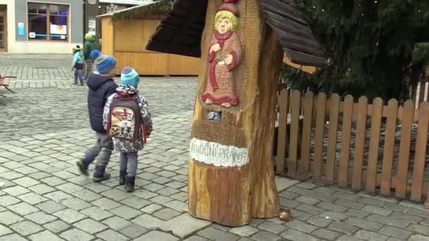 Olomouc, Česká republika, 17 prosince 2017: vyřezávaná socha malého Ježíše Krista v kmen stromu, kde děti házet vánoční přání, malé dítě staví dopis