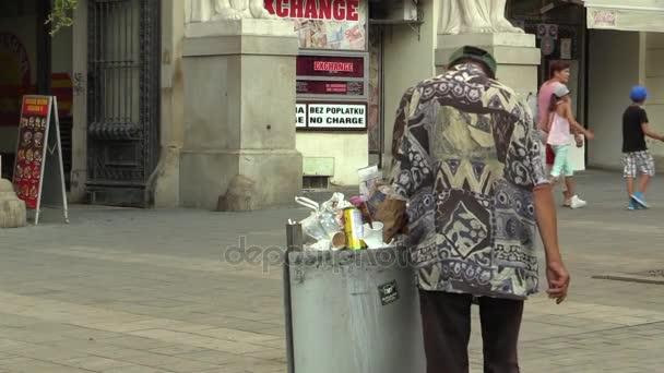 Brno, Cseh Köztársaság, 2017. augusztus 11.: hiteles hajléktalan szegény ember keres, és eszik étel a szemetet bin, Brno város, Dél-Morvaország, Csehország, Európa