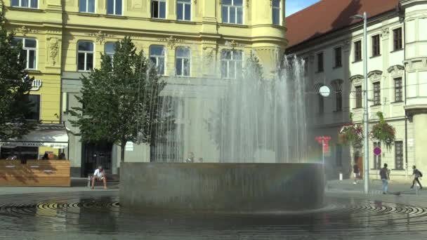 OLOMOUC, CZECH REPUBLIC, AUGUST 17, 2017: Fountain with a rainbow at Svobody square in Brno, a man in the summer heat is cooled with water, people are walking around