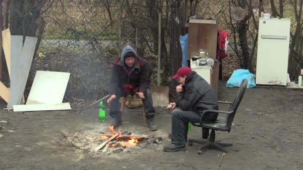 Olomouc, Česká republika, 18 ledna 2018: Bezdomovci lidé jsou chudí spalování dřeva, deska a vytváření ohně v zimě hřejí, vypálit cigarety a kouř