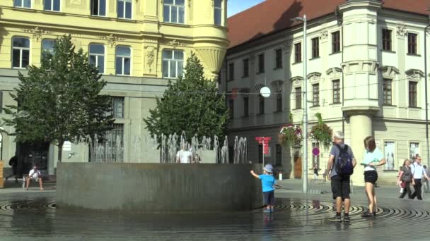 OLOMOUC, CZECH REPUBLIC, AUGUST 17, 2017: Fountain with at Svobody square in Brno, family man, child and woman in the summer heat is cooled with water, people are walking around