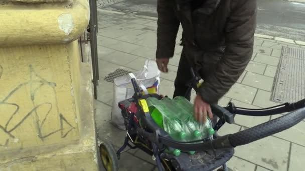 Olomouc, Česká republika, 5. března 2018: Autentické chudým bezdomovcům přináší zakoupené vinného alkoholu do plastových lahví a umístí na přepravní vozík. Velmi reálná, život na ulici