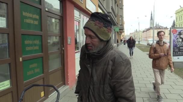 Olomouc, Česká republika, 5. března 2018: Autentické chudý bezdomovec ruka vytáhne krabici s cigaretovými zapalovači a kouř z úst osoby, kouření a lidé chodí po chodníku