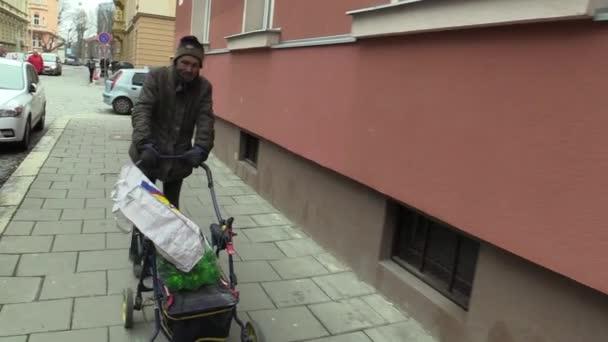 Olomouc, Česká republika, 5. března 2018: Autentické chudý bezdomovec chodí steadycam ulicí s vozík kočár, ve kterém má plastová láhev vína. Velmi reálná, život na ulici