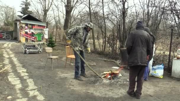 Olomouc, Česká republika, 20 března 2018: Bezdomovci chudé, připraví, spalování dřeva větev popraskané a vytvoření ohně se zahřát v zimě, žijící v horské chatě list dřevo kov