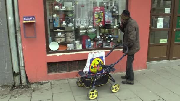 Autentické chudý bezdomovec ruky cigaretu kouří z úst osoby, kouření s vozík přepravy, při pohledu na výloze za sklem