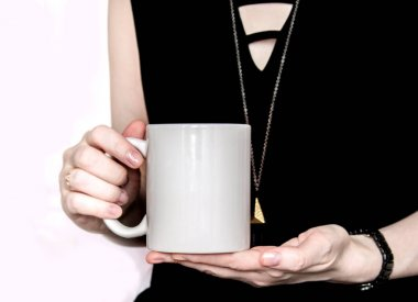 Girl in black dress is holding white cup in hands.