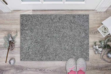 Blank grey doormat before the door in the hall. Mat on wooden floor, with christmas decoration and slippers. Welcome home, product Mockup