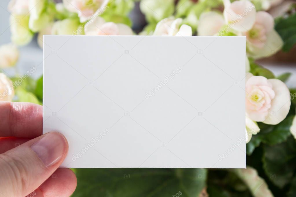 Blank white visit card template in womans hand with flowers on background. Mock-up