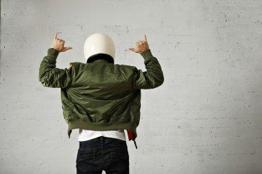 Man in helmet and bomber jacket gesturing