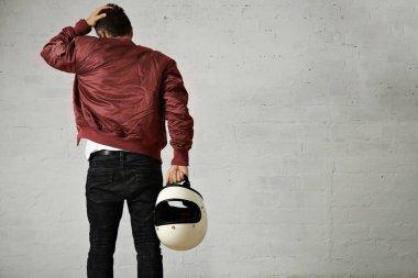 Man in a bordeaux pilot jacket with helmet