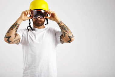 Snowboarder putting on and adjusting helmet