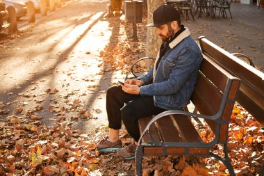 Hipster on a bench with smartphone
