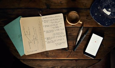 Stationery and cup of coffee on wooden table