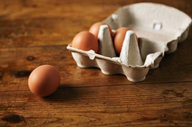 Carton of eggs on a wooden table