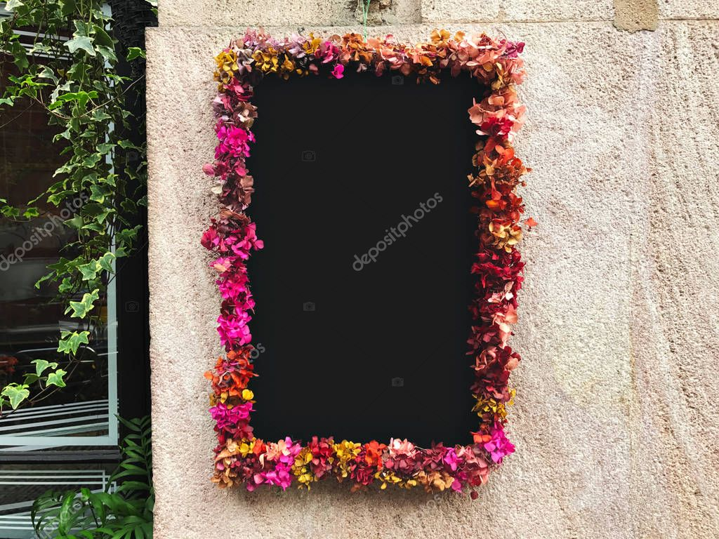Flower framed around chalkboard on stone wall