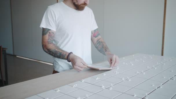 Tetovaný muž platí keramických dlaždic na kuchyňský stůl set