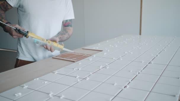 Uomo tatuato si applica piastrelle di ceramica il set da tavola