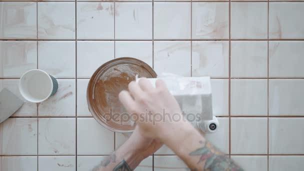 Tattooed man applies ceramic tiles on kitchen table set