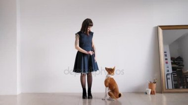 A brunette girl stands with a dog