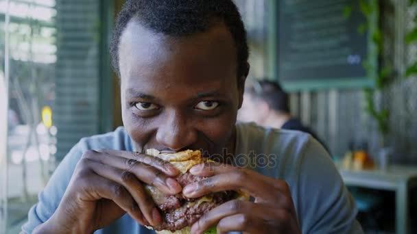 Happy černoch se smát a jí chutné maso burger
