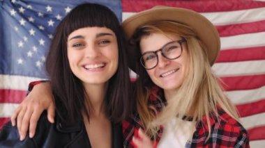 Blonde and brunette hipster girls hold a flag