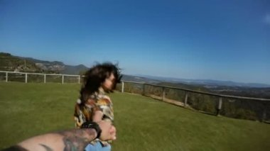 POV of a couple running in the field