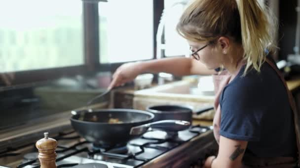 Blonde woman prepares a dish in frying pan