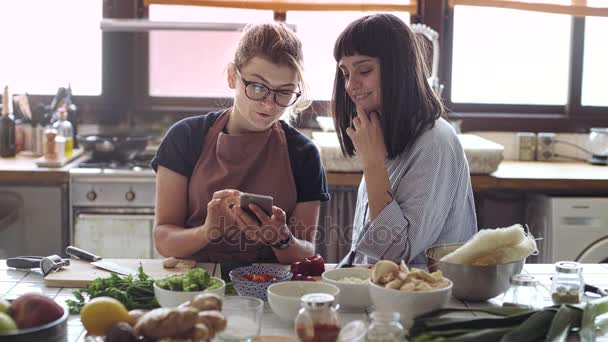 Two female friends or partners cook together