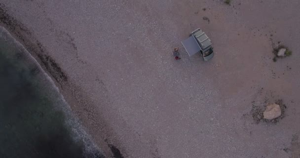 Drone footage of people and camping van