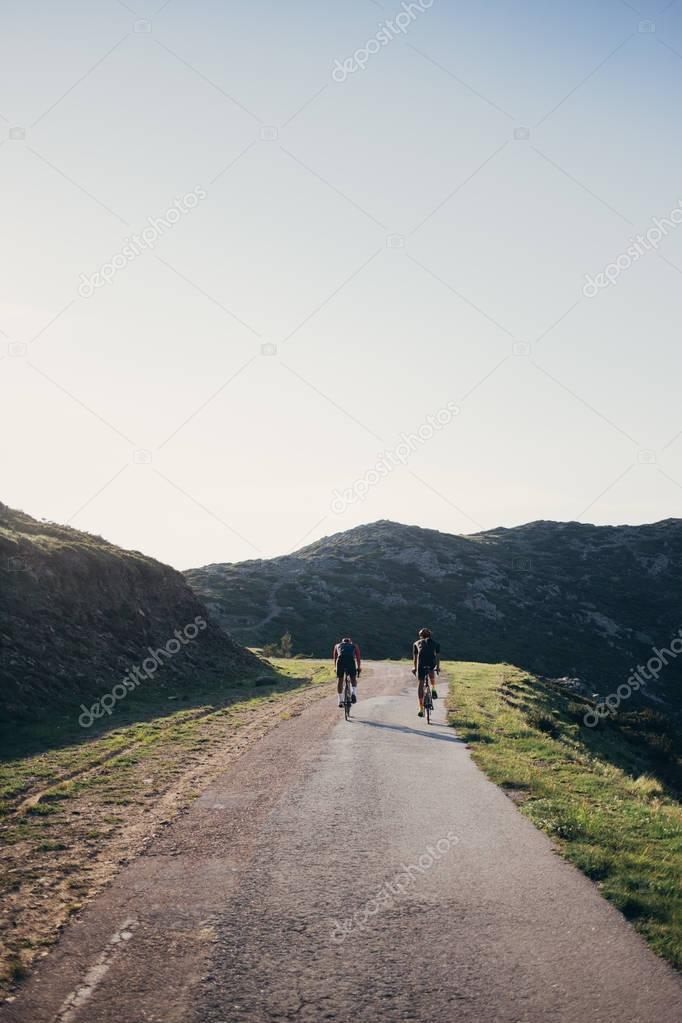 Two cyclist riding away into distance
