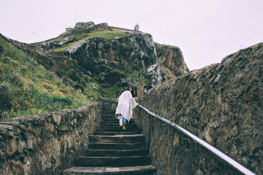 Woman climbing up stairs in mountains