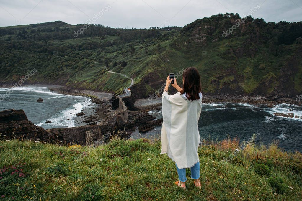 Woman taking photo on cliff