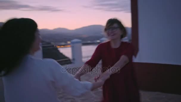 Two female friends play and dance near lighthouse