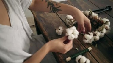 Close up of female hands work on cotton wreath