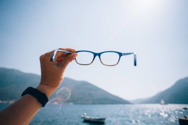 POV woman hold prescription glasses
