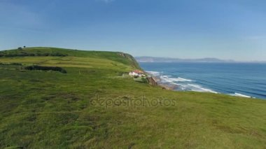 Beautiful sunny day on coast and house on cliff