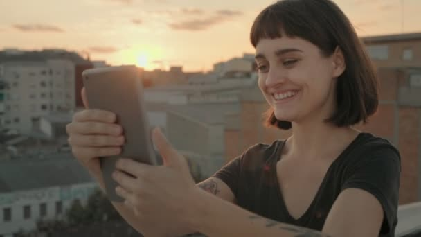 Attractive brunette with gadget on rooftop at sunset