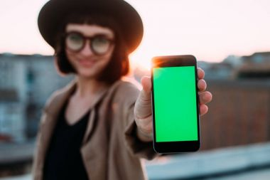 woman showing smartphone green screen