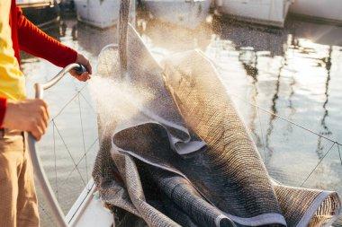 sailor man washing yacht folded sail in port