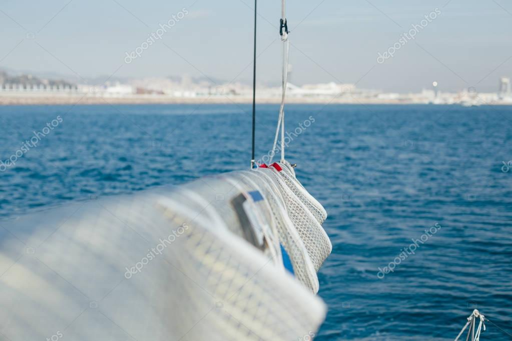 partial shot of yacht boat sailing in blue ocean water