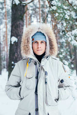 handsome Caucasian man in winter jacket looking at camera