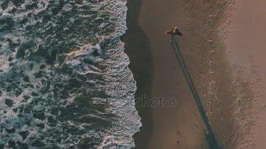 Happy girl with phone walks on seashore next to ocean