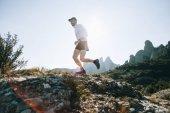 Fotografia Corridore pista professionale, distanza ultra atleta corre attraverso terreno roccioso alto sulla traccia di percorso o escursionismo di montagna, attività di stile di vita sano allaria aperta in giornata di sole. Giovane attivo nellusura di sport