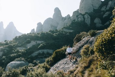 Figure or silhouette of athlete, sportsman or young runner run down a trail or path in mountains, among rocks and bushes. Enjoys fresh air and effort, sweat that turns into muscles and achievement