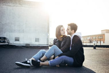Stylish and trendy hip hipsters millennials couple, boyfriend and girlfriend sit on top of rooftop at sunset, look at each other fondly. Concept relationship goals of new generation, bloggers style