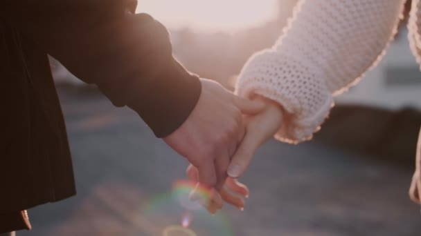 Couple holds hands in sunset light