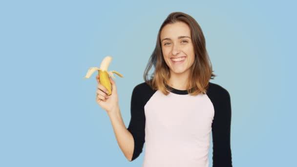 Szép, mosolygós nő tart csomó banán