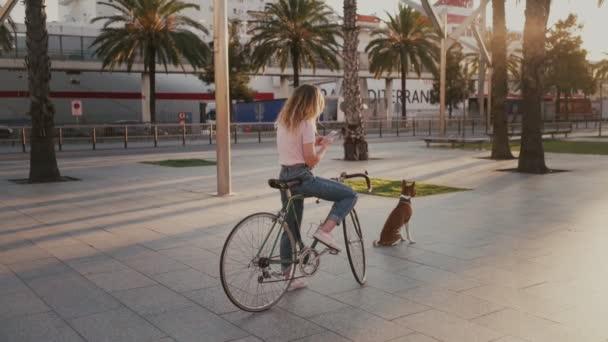 Hezká dívka na své městské Retro kolo při západu slunce